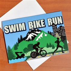 """Celebrate a big triathlon finish with our Tri Country Greeting Card.  The card features our famous tri country artwork and """"swim, bike, run"""" bold lettering.  The inside of the card is blank for your special message."""