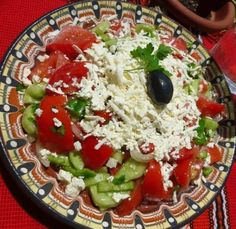 Shopska salad is probably one of Bulgaria's most iconic dishes. The salad is made of tomato, cucumber and onion. What makes it special, however, is the topping of Bulgarian white pickled cheese (sirene) Bio Yogurt, Shopska Salad, Bulgarian Yogurt, Cucumbers And Onions, Soup And Salad, Caprese Salad, Cheese, Dishes, Soups