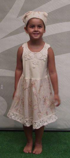 Comodísimo vestido en color crema para niña. Para completar el look, el vestido está acompañado de un pañuelo a juego.