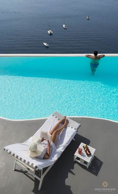 Relaxing by the luxurious infinity pool at the Katikies Hotel perched high up on the cliffs of the Santorini Caldera.