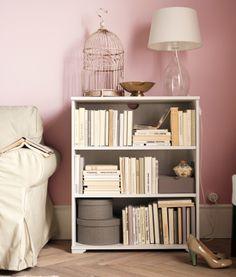 Liten IKEA bokhylla med böcker och lådor. Guldfärgad fågelbur och glaslampa ovanpå hyllan.
