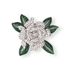A DIAMOND AND ENAMEL 'GARDENIA' BROOCH, BY OSCAR HEYMAN & BROTHERS    Designed as a pavé-set diamond flower with green enamel leaves, mounted in white gold, 5.0 cm wide