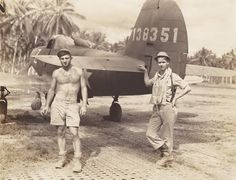 """This is P-39D, s/n 41-38351 A pilot and ground crewman stand by the tail of this airplane, squadron code """"Z."""" Both men wear heavy combat boots. The enlisted man is holding a cigarette; the pilot is wearing a Mae West and a shoulder holster. Note the Marston mat (pierced steel planking), which the engineers laid down to make serviceable runways quickly."""