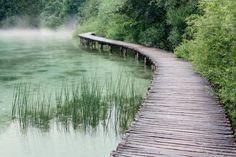Misty nostalgic boardwalk over a pond