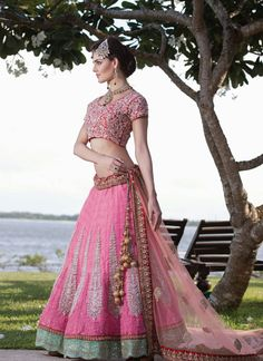 Create a smoldering impression on everyone with this Pink Colour Net Bridal Lehenga Choli.The attractive designs of embroidery enhanced with resham work, zari work along with sequins, applique designs and patch border work enchants beauty. Paired with matching choli and dupatta.