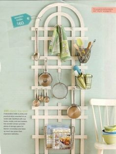 Add cup hooks, knobs and wire baskets to store kitchen ware on a garden trellis - maybe the trivet collection?