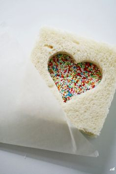 Fairy bread with a heart! The website is in French and I couldn't find the original photo but fairy bread is easy to make. Just spread butter a loaf of bread and cover with sprinkles or hundreds and thousands which stick to the butter.  Use a heart cookie cutter on the second slice of bread and you have a Sweet Valentine Treat for you little ones!