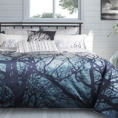 Home Republic Blueridge  Bedding Collection: Capturing an early morning walk through the trees of a misty forest, Blueridge brings the outdoors in with colours of indigo and a blue-teal ombré graduating to white. Printed on 100% cotton sateen, this design reverses to a detailed woodgrain pattern in shades of blue-grey and white.