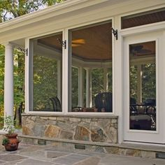 by Winn Design & Remodeling  This screen porch was constructed with a stone base, composite trim/moldings and a stained-cypress ceiling with a droppe.