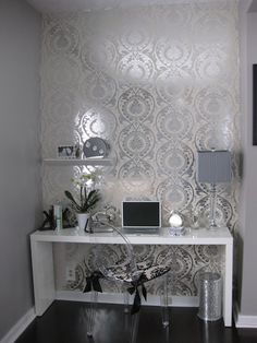 I love this concept for a desk or vanity area. Patterned foil accent wall, white desk, crystal lamp, orchid arrangement, ghost chair, silver wastebasket. Everything is so right!