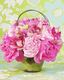 A variety of feminine flowers, including peonies and sweet peas, were used here. Place the focal flowers, such as luscious peonies, in the bouquet first.  Work with one variety at a time, concentrating on the large blooms first, easing into the medium-size blooms, and then to the smallest varieties.  Shop in monochromatic color stories, only breaking away with an occasional pop of green. Group them in a cluster style so it feels refined, compact, and abundant.