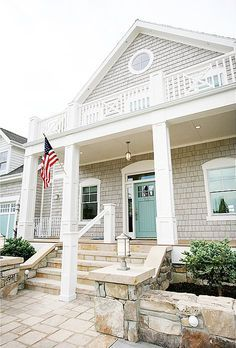 Love the light grey exterior and the beachy blue door! Very pretty.