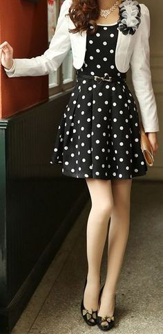 Very cute 50's inspired look with the black and white polka dot dress, black heels and the white jacket with the flower details.