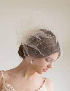 This two layer birdcage veil was handcrafted using high quality illusion tulle attached to a silver metal comb. They bottom layer is 18 and the