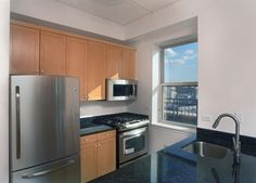 Granite countertops and stainless steel appliances in a modern Soho Court Luxury Apartments in Soho NYC.
