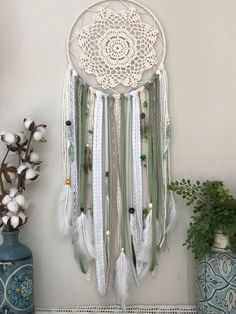 "This large green dream catcher is the perfect addition to a beautiful nights sleep. This boho style dream catcher is made up of green, white and ivory ribbons, lace and yarn. The addition of natural stones and feathers bring this dream catcher to life. This style includes three hand painted feathers with bohemian designs. Measuring at 10"" wide by 30"" long this wall hanging is sure to keep all the bad dreams away! To customize any details go to www.shopwildcotton.com. Sweet Dreams!"