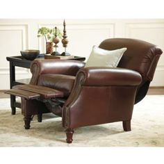 """Theodore Leather Recliner The stately lines and substantial proportions 37 1/4""""H X 35""""W X 36 1/2""""D & 64""""D Hand crafted hardwood frame is richly padded and covered in supple, full–grain chocolate leather that will deepen in character over time. Hand applied brass tack trim accentuate its classic rolled arms and tailored skirt. Adjusts to 3 relaxing positions with a gentle push 8–way hand–tied springs Legs are finished in Chestnut stain Imported $1249"""