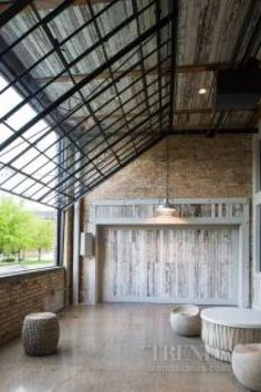City warehouse loft conversion with exposed brick and timber structural columns. This porch on the ground floor of a converted 100-year-old laundry building. The bricks and wood have a whitewashed finish. By Chris Hawley Architects.