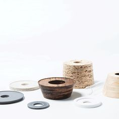 Collection of vases made from layers of materials stacked in different combinations. Nir Meiri stacks Babilus Vases from rings of bamboo, chipboard and Corian.