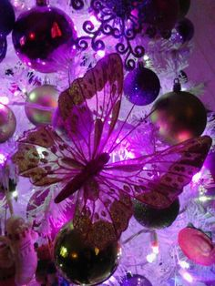 LED purple and pink decorations on white Christmas tree. With pin on butterflies and purple and pink bulbs.