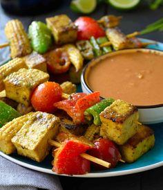 Brochetas vegetarianas marinadas en una deliciosa salsa de coco, curry y lima. Servido con una salsa de cacahuete. Un plato vegano para servir de picoteo.