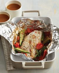"""Steamed Red Snapper Packets - Jamaicans call this dish """"roast fish,"""" even though the seafood actually steams in a foil packet with vegetables. It is served with a side of """"fish tea""""—a broth similar to bouillabaisse that's eaten as a kind of sauce."""
