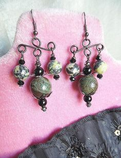Unusually Different Victorian Goth Chandelier Earrings! I decided to create these earrings with wonderful, large snakeskin jasper beads with varying shades of green and a touch of brown, as the center drop ( 1/2 in width ), centered between two black onyx beads, gunmetal bead caps, and gunmetal crystals. The beads on each side drop are a lovely pale yellow green and black serpentine, with black crystals on the top and bottom of each drop. The wire frames of the earrings are gunmetal enam...