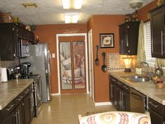 Love the burnt orange walls against the dark cabinets. Doing this next break i GET! Refinishing my cabinets, and DIYing my countertops! Bistro Kitchen, Home Decor Kitchen, Kitchen Design Decor, Bistro Kitchen Decor, Kitchen Remodel, Kitchen Wall Colors, Home Decor, Kitchen Renovation, Orange Kitchen Walls