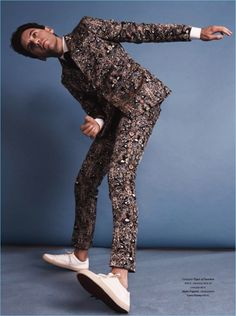Embracing an all-over print look, Mika wears a Tiger of Sweden shirt, suit, and tie with Loro Piana shoes.