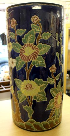 1920's ceramic stick/umbrella stand. Good condition. No chips or restoration. Decorated with a lovely floral pattern on a bright vibrant blue background. Very sturdy piece. Height measures 19.5 inches. Top diameter measures just over 9 inches.