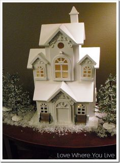 A lighted Christmas cottage sits on a side table in the dining room
