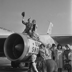 Bob Hope and actress Jill St. John perch on jet engine before taking off from Los Angeles International Airport on flight to Southeast Asia for 13th annual two-week Christmas tour of U.S. military bases. Others making the trip are, from left, Pat Shelly, with elephant, Anita Bryant, Jerry Colona, Janice Paige, Ann Sydney, Miss World of 1964, and Anna Maria Alberghetti. (Publication: Los Angeles Times - Publication date: December 16, 1964)
