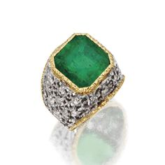EMERALD AND DIAMOND RING, BUCCELLATI Set with an emerald-cut emerald weighing approximately 8.00 carats, within a raised openwork frame accented with small round diamonds, mounted in 18 karat yellow and white gold