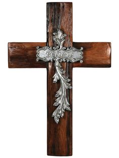 """Real wooden cross with poly resin embellishments. The word """"Believe"""" is carved into the ornate leaf-scrolled faux metallic accents. The wood is finished in a be"""
