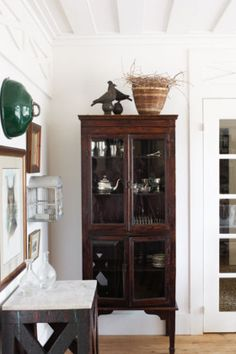 Love this dark cabinet to display silver. Very dramatic yet stays within the rustic theme.
