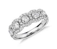 Five stone ring encircled by brilliant pavé-set diamond halos in this eye-catching 18k white gold wedding ring.