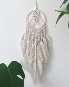 This macrame dream catcher is made of cotton and a wrapped silver craft frame. This modern bohemian macrame dream catcher with 7 macrame feathers looks great, from the ceiling or the wall, over your bed or in a window. The length is 52 cm and the widt Macrame Wall Hanging Patterns, Wall Hanging Crafts, Macrame Plant Hangers, Macrame Patterns, Macrame Design, Macrame Art, Macrame Projects, Macrame Knots, Art Macramé