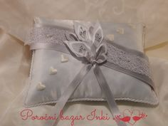silver and white wedding ring pillow