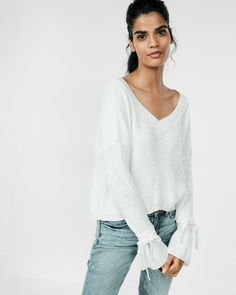 A cozy-chic sweater with long bell sleeves and a sexy split back. We love it with high-waisted denim and glitzy accessories.