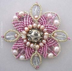 Pin in sterling silver wire, with silver central bead, crystals, pearls and vintage cut seed Read more
