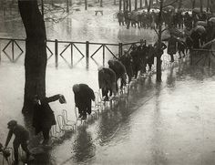 Henri Manuel  The Maison Laffitte hippodrome, west of Paris, is flooded by the flood of the Seine. Jockeys and others find the typical french chairs under the trees, a safe haven. Paris, 1924.