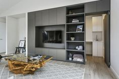 Entertainment unit with storage, leading into the laundry. Transportable home with push to open doors. Melamine fronts.