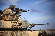Marine with Battalion Landing Team Battalion, Marine Regiment, Marine Expeditionary Unit (MEU), shoots at targets with an machine gun from a light armored vehicle during a live-fire exercise as part of Exercise Eager Lion 2014