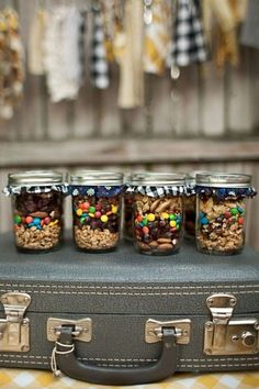 Cute idea for a rustic wedding, with a destination theme.. Trail Mix Mason Jars displayed on a suitcase! !