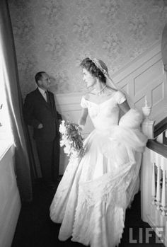 Jackie Bouvier in Kennedy wedding dress-- I love the classic portrait neckline and fitted bodice with full skirt (emphasis the tiny waist...perfect for my figure) but not the fuzziness of the Battenburg lace cut work of the overly detailed skirt.