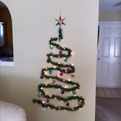 space-saving christmas tree made of pre-lit garland thumbtacked to the wall!