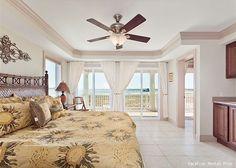 Luxury master bedroom with king bed, ocean views & wet bar
