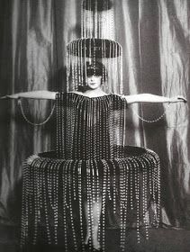 One of Paul Poiret's fancy dresses, this Fountain costume was worn by Marchesa Luisa Casati, an Italian heiress and, by her own account, 'a living work of art'.  Consists of an elaborate two-storey hat and strings of large beads streaming down the body and the hoop skirt.