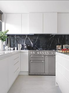 Create drama in a functional yet sleek white modern kitchen, with a beautiful black marble splashback. A large range cooker is a must-have for a serious chef, and looks gorgeous too! Modern Kitchen Interiors, Modern Kitchen Design, Interior Design Kitchen, Modern Design, Interior Decorating, Decorating Ideas, Kitchen On A Budget, Home Decor Kitchen, New Kitchen
