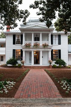Beautiful white two-story colonial house with a double balcony, flower box, and brick pathway.